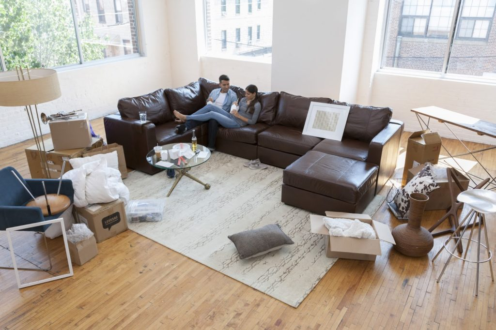 Couple on sectional sofa moving in